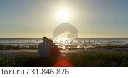 Купить «Rear view of romantic couple sitting at beach 4k», видеоролик № 31846876, снято 20 сентября 2018 г. (c) Wavebreak Media / Фотобанк Лори