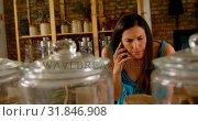 Купить «Beautiful woman talking on mobile phone in supermarket 4k», видеоролик № 31846908, снято 13 сентября 2018 г. (c) Wavebreak Media / Фотобанк Лори