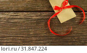 Купить «Bouquet of red roses on envelope with red ribbon on wooden surface 4k», видеоролик № 31847224, снято 11 октября 2018 г. (c) Wavebreak Media / Фотобанк Лори