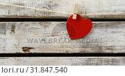 Купить «Red heart paper cut pinned on the rope against wooden surface 4k», видеоролик № 31847540, снято 11 октября 2018 г. (c) Wavebreak Media / Фотобанк Лори
