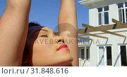 Купить «Front view of young mixed-race woman doing yoga in backyard of home 4k», видеоролик № 31848616, снято 7 ноября 2018 г. (c) Wavebreak Media / Фотобанк Лори