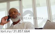 Купить «Front view of mature black man talking on mobile phone in a comfortable home 4k», видеоролик № 31857664, снято 7 ноября 2018 г. (c) Wavebreak Media / Фотобанк Лори