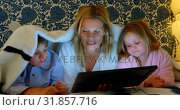Купить «Front view of young Caucasian mother with her son and daughter using digital tablet on bed in bedroo», видеоролик № 31857716, снято 6 ноября 2018 г. (c) Wavebreak Media / Фотобанк Лори