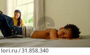 Купить «Black father helping his son changing his clothes on bed in a comfortable home 4k», видеоролик № 31858340, снято 19 октября 2018 г. (c) Wavebreak Media / Фотобанк Лори