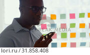 Купить «Side view of young black businessman talking on mobile phone in a modern office 4k», видеоролик № 31858408, снято 6 октября 2018 г. (c) Wavebreak Media / Фотобанк Лори