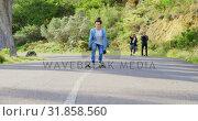 Купить «Front view of cool young caucasian man doing skateboard trick on downhill at countryside road 4k», видеоролик № 31858560, снято 16 октября 2018 г. (c) Wavebreak Media / Фотобанк Лори