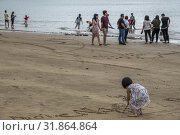 Girl draws pictures on the beach, Telok Melano , Sematan, Sarawak, Malaysia (2019 год). Редакционное фото, фотограф Chua Wee Boo / age Fotostock / Фотобанк Лори