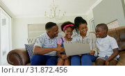 Купить «Front view of young black family sitting on the couch and using laptop in a comfortable home 4k», видеоролик № 31872456, снято 7 ноября 2018 г. (c) Wavebreak Media / Фотобанк Лори
