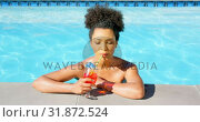 Купить «Front view of young mixed-racewoman drinking cocktail in swimming pool 4k», видеоролик № 31872524, снято 7 ноября 2018 г. (c) Wavebreak Media / Фотобанк Лори