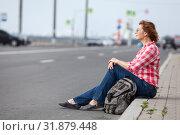 Купить «Mature woman hitchhiker sitting on roadside and waiting the car», фото № 31879448, снято 21 июня 2019 г. (c) Кекяляйнен Андрей / Фотобанк Лори
