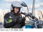 Купить «Woman motorcycle traveler finding the location in navigator device, sitting on her bike», фото № 31880304, снято 15 сентября 2018 г. (c) Кекяляйнен Андрей / Фотобанк Лори