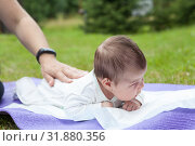 Купить «Newborn baby lying on white blanket on lawn and first time holds head straight, mother hand pats on the back», фото № 31880356, снято 17 июля 2019 г. (c) Кекяляйнен Андрей / Фотобанк Лори