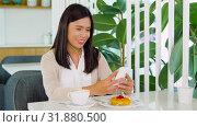 Купить «asian woman with smartphone and earphones at cafe», видеоролик № 31880500, снято 21 июля 2019 г. (c) Syda Productions / Фотобанк Лори