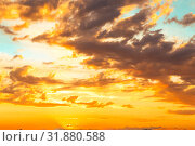 Купить «Beautiful bright majestic dramatic evening sky at sunset orange color with rays. The sun shines over the horizon against the backdrop of thunderclouds at dusk», фото № 31880588, снято 28 июня 2019 г. (c) Светлана Евграфова / Фотобанк Лори