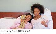 Купить «Front view of black mother and daughter reading story book in a comfortable home 4k», видеоролик № 31880924, снято 7 ноября 2018 г. (c) Wavebreak Media / Фотобанк Лори