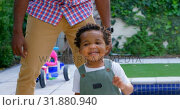 Купить «Front view of young black father and little son playing in back yard of their home 4k», видеоролик № 31880940, снято 19 октября 2018 г. (c) Wavebreak Media / Фотобанк Лори