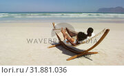 Купить «Couple interacting with each other while lying in a hammock 4k», видеоролик № 31881036, снято 14 ноября 2018 г. (c) Wavebreak Media / Фотобанк Лори