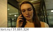 Купить «Front view of young caucasian businesswoman talking on mobile phone and walking in modern office 4k», видеоролик № 31881324, снято 13 октября 2018 г. (c) Wavebreak Media / Фотобанк Лори