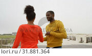 Купить «Young romantic black couple dancing together on promenade at beach on a sunny day 4k», видеоролик № 31881364, снято 14 ноября 2018 г. (c) Wavebreak Media / Фотобанк Лори
