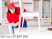 Купить «Young woman repairing chair at home», фото № 31881992, снято 19 марта 2019 г. (c) Elnur / Фотобанк Лори