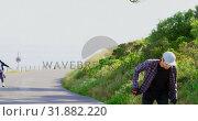 Купить «Front view of cool young caucasian skateboarders skating on downhill at countryside 4k», видеоролик № 31882220, снято 16 октября 2018 г. (c) Wavebreak Media / Фотобанк Лори