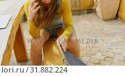 Купить «Front view of young caucasian woman with skateboard talking on mobile phone at outdoor cafe 4k», видеоролик № 31882224, снято 16 октября 2018 г. (c) Wavebreak Media / Фотобанк Лори