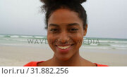 Купить «Front view of young black woman smiling and looking at camera on the beach 4k», видеоролик № 31882256, снято 14 ноября 2018 г. (c) Wavebreak Media / Фотобанк Лори