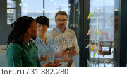 Купить «Business executives discussing over sticky note in office 4k», видеоролик № 31882280, снято 16 июня 2018 г. (c) Wavebreak Media / Фотобанк Лори