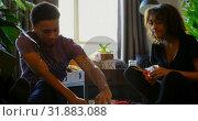 Купить «Front view of mixed-race young couple wrapping gift box in a comfortable home 4k», видеоролик № 31883088, снято 2 октября 2018 г. (c) Wavebreak Media / Фотобанк Лори