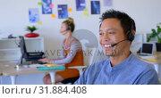 Купить «Young Asian male executive talking on headset at desk 4k», видеоролик № 31884408, снято 18 ноября 2018 г. (c) Wavebreak Media / Фотобанк Лори