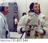 Купить «USA Capr Canaveral -- 16 Jul 1969 -- Apollo 11 Commander Neil Armstrong prepares to put his helmet on shortly before the historic launch of the Apollo...», фото № 31897544, снято 17 августа 2019 г. (c) age Fotostock / Фотобанк Лори