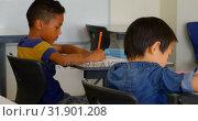 Купить «Multi-ethnic schoolkids studying at desk in a classroom at school 4k», видеоролик № 31901208, снято 10 ноября 2018 г. (c) Wavebreak Media / Фотобанк Лори