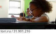 Купить «Side view of African american schoolgirl studying at desk in classroom at school 4k», видеоролик № 31901216, снято 10 ноября 2018 г. (c) Wavebreak Media / Фотобанк Лори