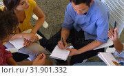 Multi-ethnic business colleagues writing on a diary in modern office 4k. Стоковое видео, агентство Wavebreak Media / Фотобанк Лори