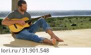 Купить «Front view of caucasian man playing guitar at porch of beach house 4k», видеоролик № 31901548, снято 22 июня 2018 г. (c) Wavebreak Media / Фотобанк Лори