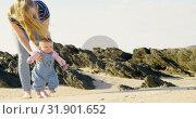 Купить «Front view of mid adult caucasian mother helping baby to walk at beach on a sunny day 4k», видеоролик № 31901652, снято 22 июня 2018 г. (c) Wavebreak Media / Фотобанк Лори
