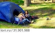 Купить «Female hikers interacting with each other near tent in the forest 4k», видеоролик № 31901988, снято 12 октября 2018 г. (c) Wavebreak Media / Фотобанк Лори