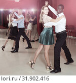 Купить «Positive adult couples dancing tango together in modern studio», фото № 31902416, снято 4 октября 2018 г. (c) Яков Филимонов / Фотобанк Лори