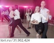 Adult pairs practicing salsa movements in modern dance studio. Стоковое фото, фотограф Яков Филимонов / Фотобанк Лори