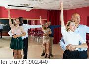 Купить «Portrait of positive adult pairs enjoying tango in modern dance hall», фото № 31902440, снято 4 октября 2018 г. (c) Яков Филимонов / Фотобанк Лори