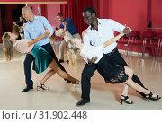 Купить «Adult pairs dancing tango movements in modern dance studio», фото № 31902448, снято 4 октября 2018 г. (c) Яков Филимонов / Фотобанк Лори