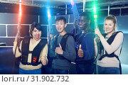 Купить «Glad group having fun on dark lasertag arena», фото № 31902732, снято 23 января 2019 г. (c) Яков Филимонов / Фотобанк Лори