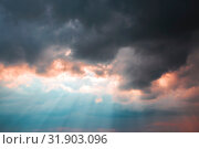 Купить «Heavenly dramatic landscape background. Bad weather, thunderstorm, clouds, storm. The concept of the struggle of light and darkness. The shining of the sun's rays in the blue sky through the black clouds in the evening at sunset», фото № 31903096, снято 28 июня 2019 г. (c) Светлана Евграфова / Фотобанк Лори