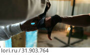 Купить «African American male trainer assisting boxer in wearing hand wrap in gym 4k», видеоролик № 31903764, снято 17 октября 2018 г. (c) Wavebreak Media / Фотобанк Лори