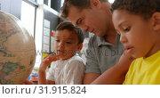 Купить «Side view of young Caucasian male teacher teaching kids about geography with globe in classroom 4k», видеоролик № 31915824, снято 17 ноября 2018 г. (c) Wavebreak Media / Фотобанк Лори