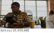 Купить «Male graphic designer reviewing photos on digital camera at desk 4k», видеоролик № 31919440, снято 6 декабря 2018 г. (c) Wavebreak Media / Фотобанк Лори