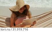 Купить «Front view of Caucasian woman using digital tablet in a hammock at beach 4k», видеоролик № 31919716, снято 12 ноября 2018 г. (c) Wavebreak Media / Фотобанк Лори