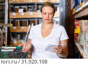 Купить «Young female holding shop list and choosing tools at shelves in build store», фото № 31920108, снято 20 сентября 2018 г. (c) Яков Филимонов / Фотобанк Лори