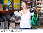 Купить «Woman customer holding purchases and walking in modern build store», фото № 31920128, снято 20 сентября 2018 г. (c) Яков Филимонов / Фотобанк Лори