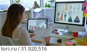 Купить «Rear view of Caucasian female fashion designer working on computer at desk in office 4k», видеоролик № 31920516, снято 18 ноября 2018 г. (c) Wavebreak Media / Фотобанк Лори